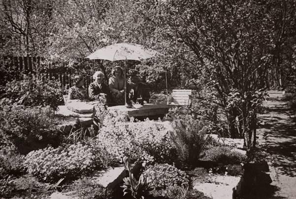 Elo ja Friedebert Tuglas ning Elo Kurvits päikesevarju all aias (1959). Foto: P. Horma. Underi ja Tuglase Kirjanduskeskus